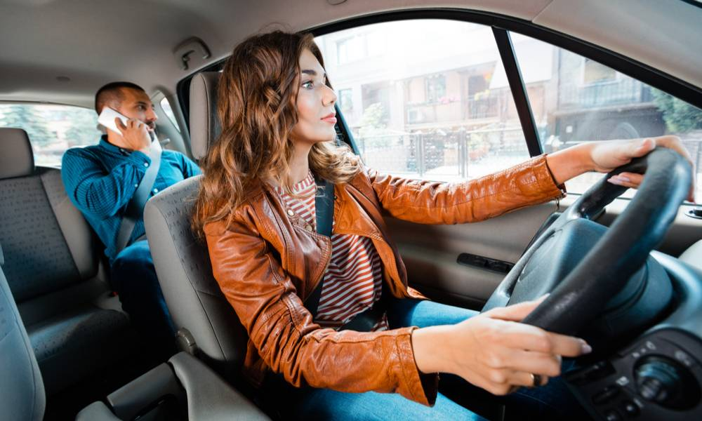 Female driving a car with male passenger talking on mobile phone in the background.jpeg