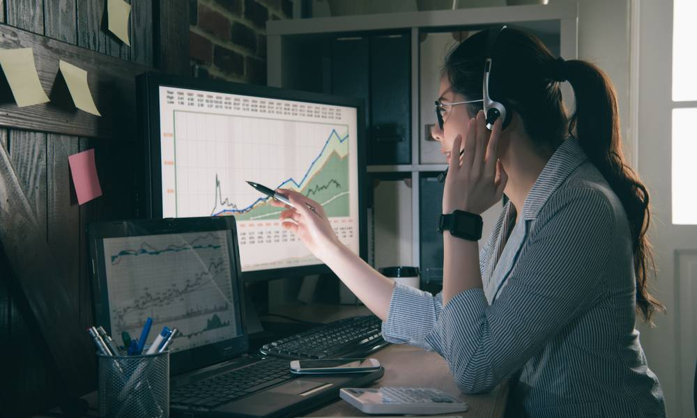 A trader wears headphones while looking at a stock chart.jpeg