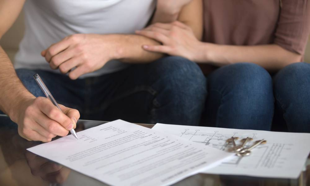 Close up of loving couple signing rental agreement or sale purchase contract sitting on couch indoors, starting family life, approved loan to buy real estate.jpeg