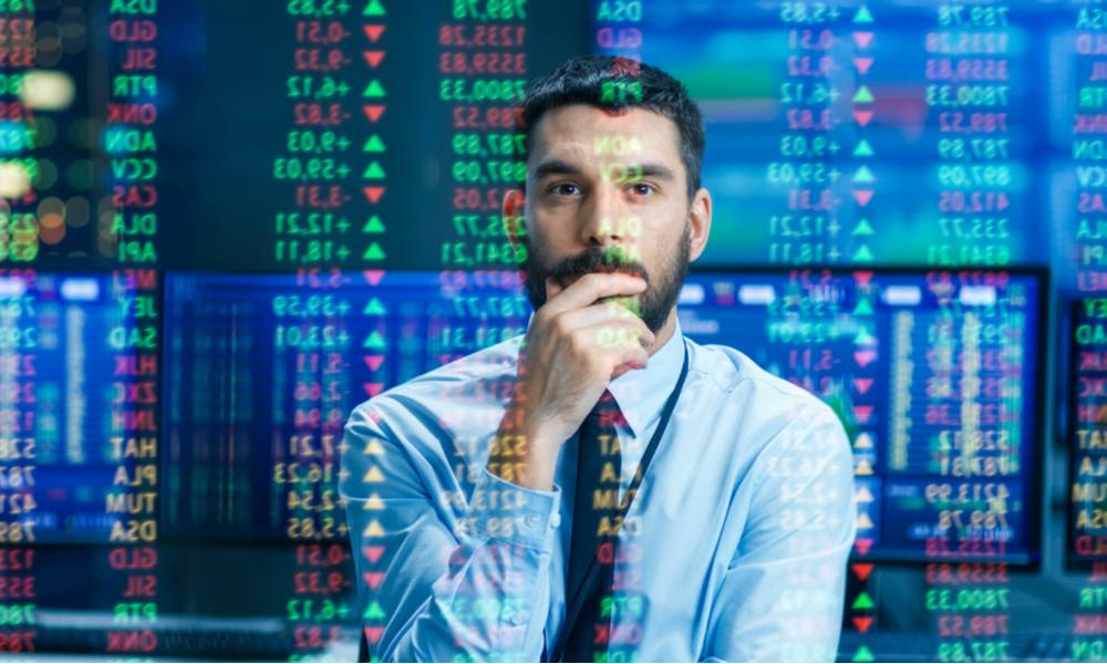 Stock market trader examines projected ticker numbers and graphs (1).jpg