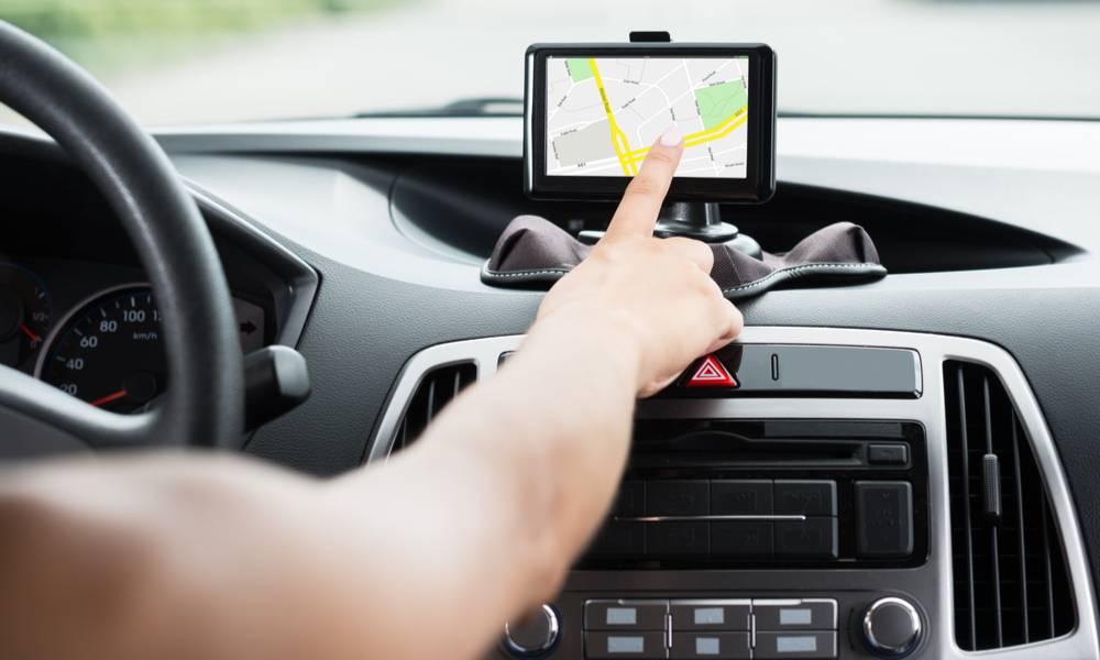 Close-up of hand using GPS navigation inside a car (1).jpg
