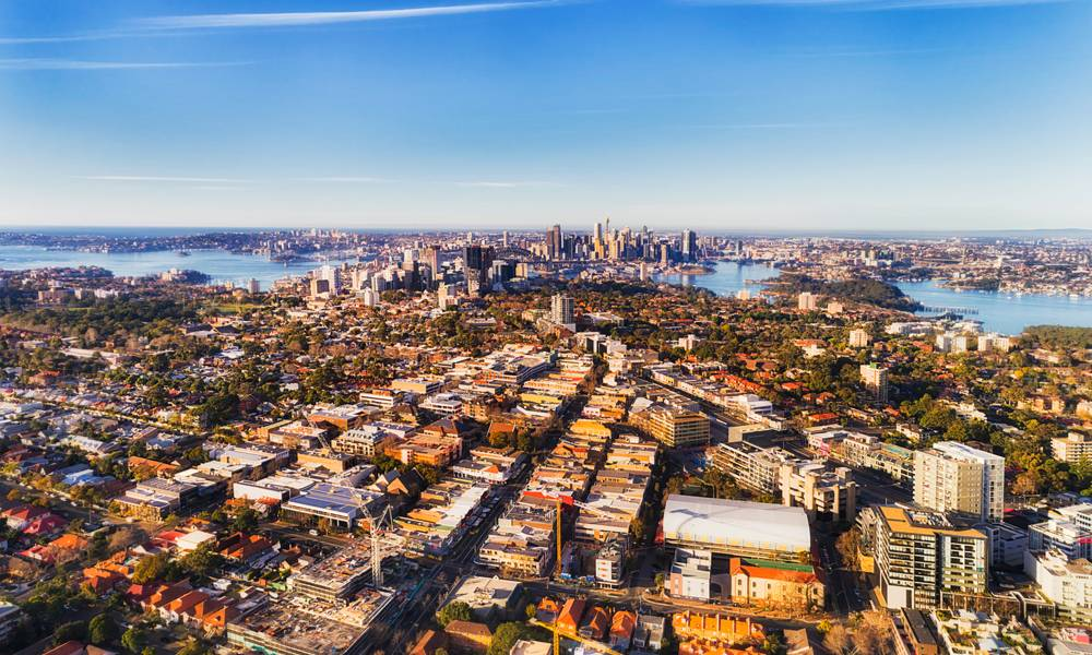 Local residential suburbs in Inner city of Sydney on shores of Sydney harbour viewed from above mid-air on a sunny day facing CBD landmarks.jpg