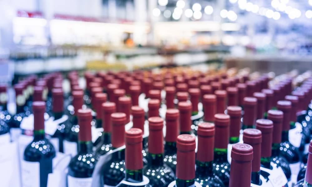Blurred and close up view group of red wine bottles in cellar at wine section of modern distribution warehouse.jpg