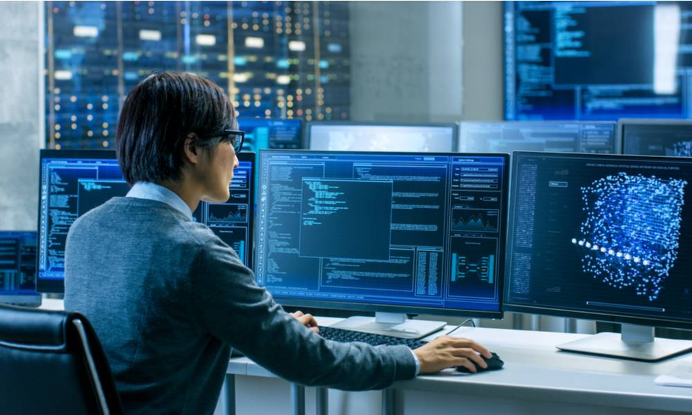 Technical operator works at workstation with multiple displays showing graphics in the control room..jpg