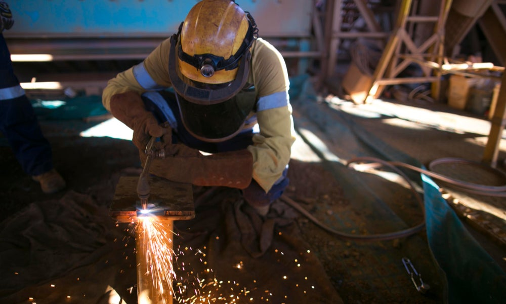 Construction worker cutting steel plate at mining site-min.jpg