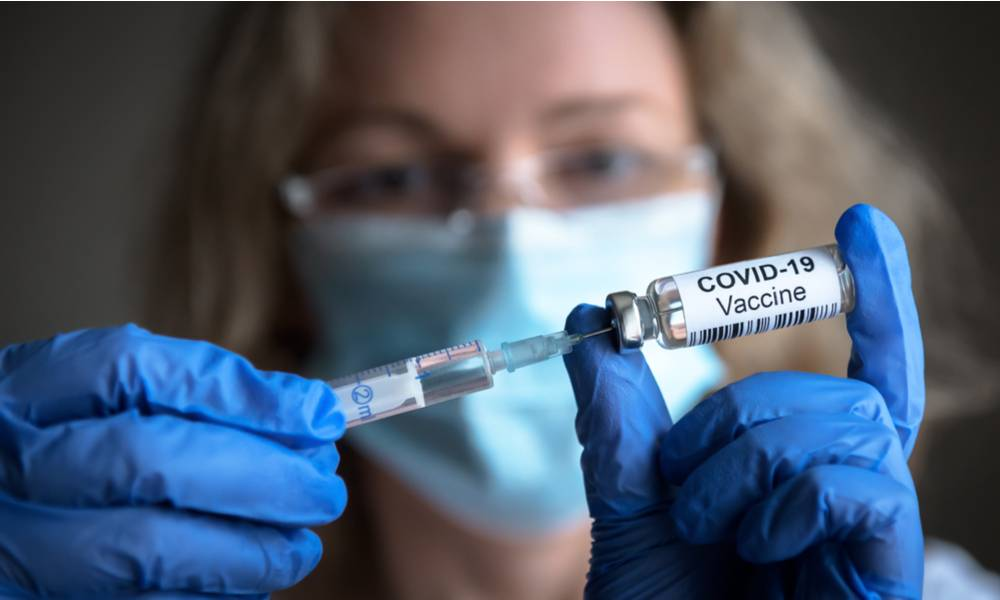 Health worker hold COVID-19 vaccine and syringe in hand (1).jpg