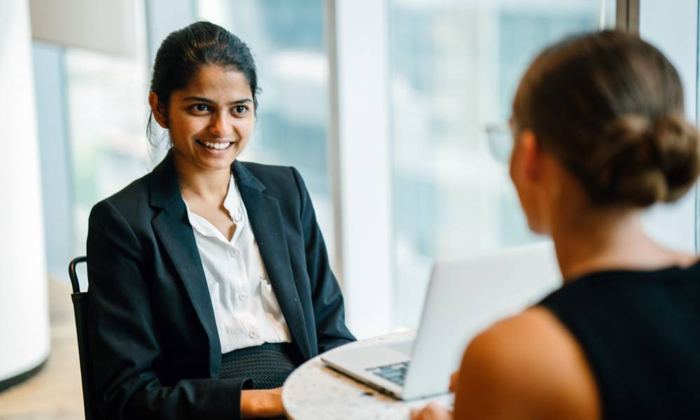 A young Indian Asian woman has a business meeting (interview) with a Caucasian white woman in an office during the day..jpg