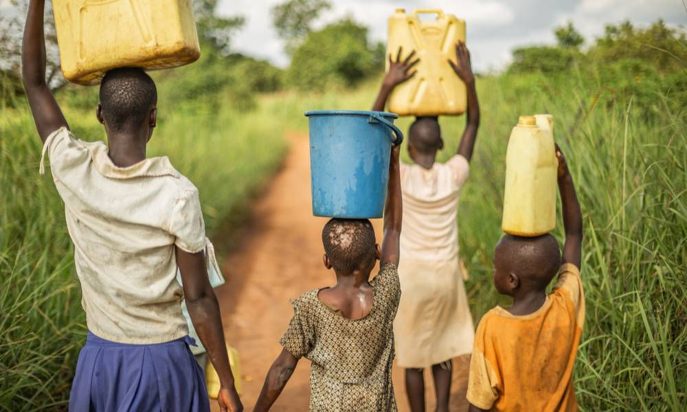 Group of young African children walking with buckets and jerrycans on their head as they prepare to bring clean water back to their village.jpg