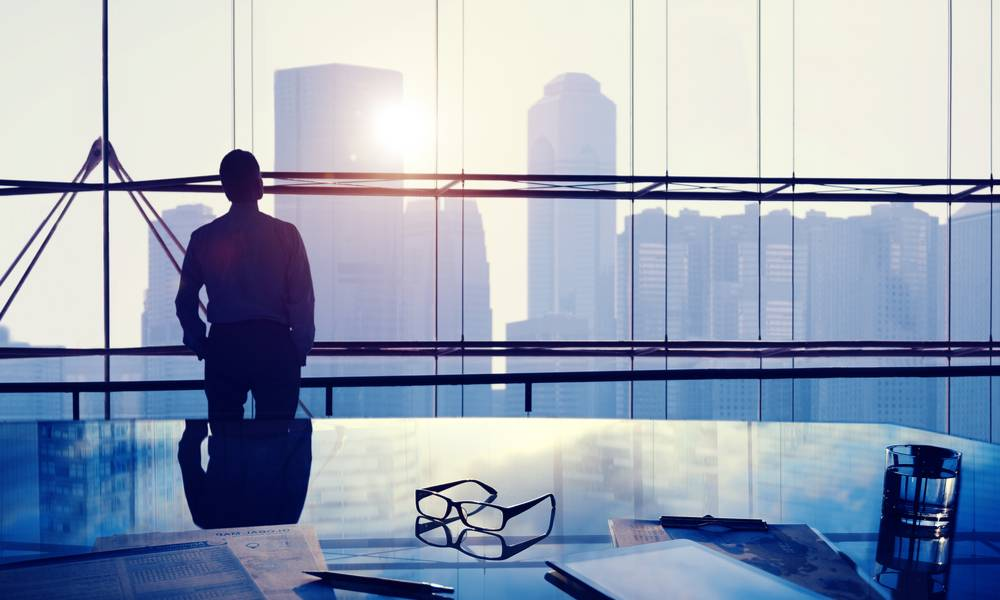 Businessman thinking inside coirporate office with view of city skyline (1).jpg