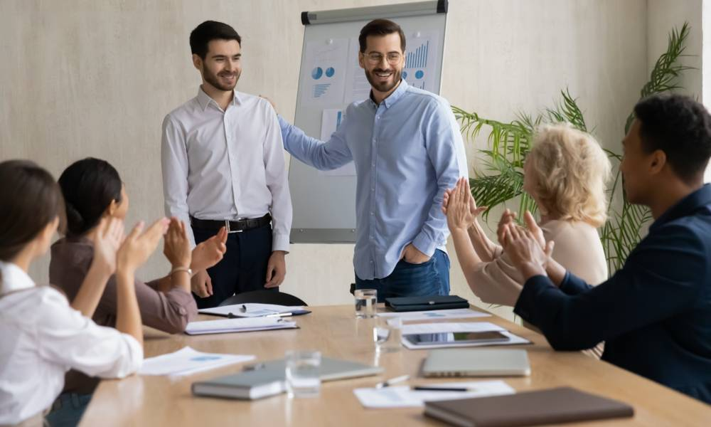 Happy young businessman introduces new male employee newcomer at office meeting, man boss congratulate worker with promotion or achievement, colleagues applaud (1).jpg