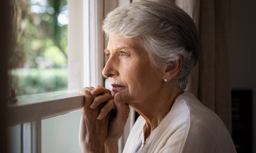An ageing woman looks out of window depressed.jpeg
