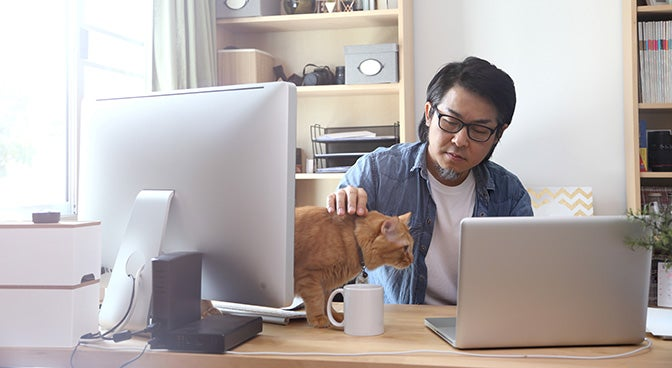 a man sat at a desk whilst stroking a cat that is on the desk