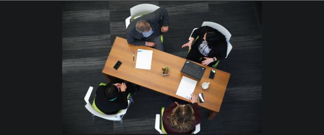 ein Blick von oben auf die Mitarbeiter in einer Besprechung