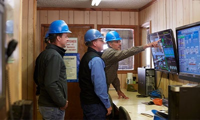 group of men talking discussing information on a digital screen