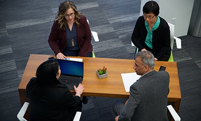 an over head view of three women and a male discussing at a desk