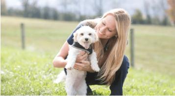 eine Person, die ihren Hund hält, während sie auf einem Feld kniet