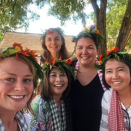 five women smiling at the camera with flower arrangements on their heads