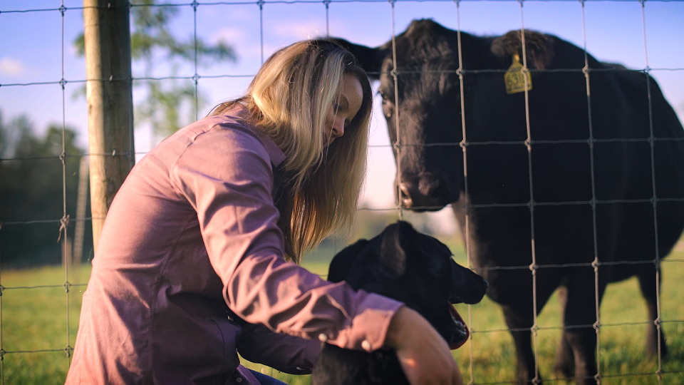 A women knelt down petting her dog while the face cattle in a field