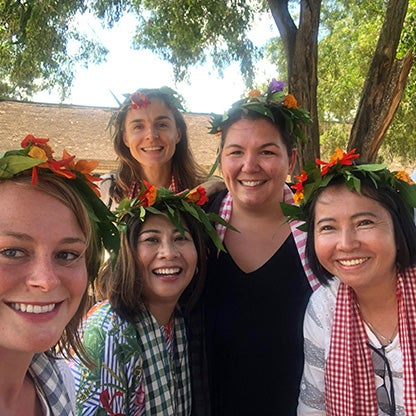 image of five women smiling at the camera with a flower arrangement on their heads