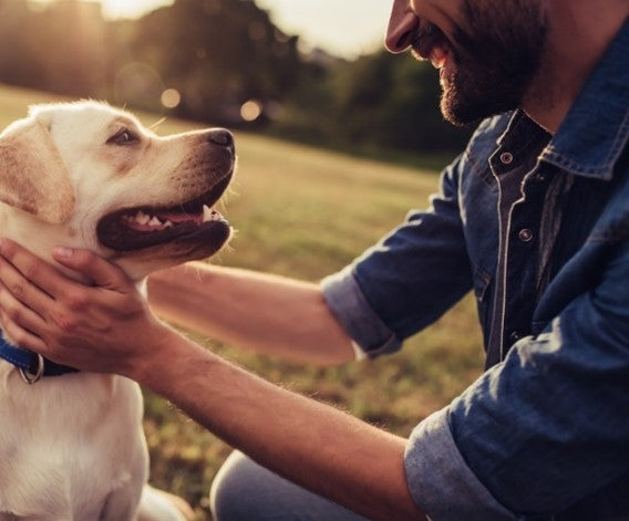Man smiling by holding a dog