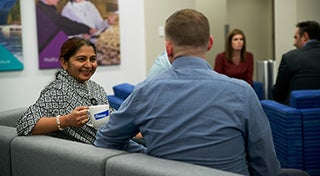 woman smiling at a male sat down in a waiting room holding an Elanco mug