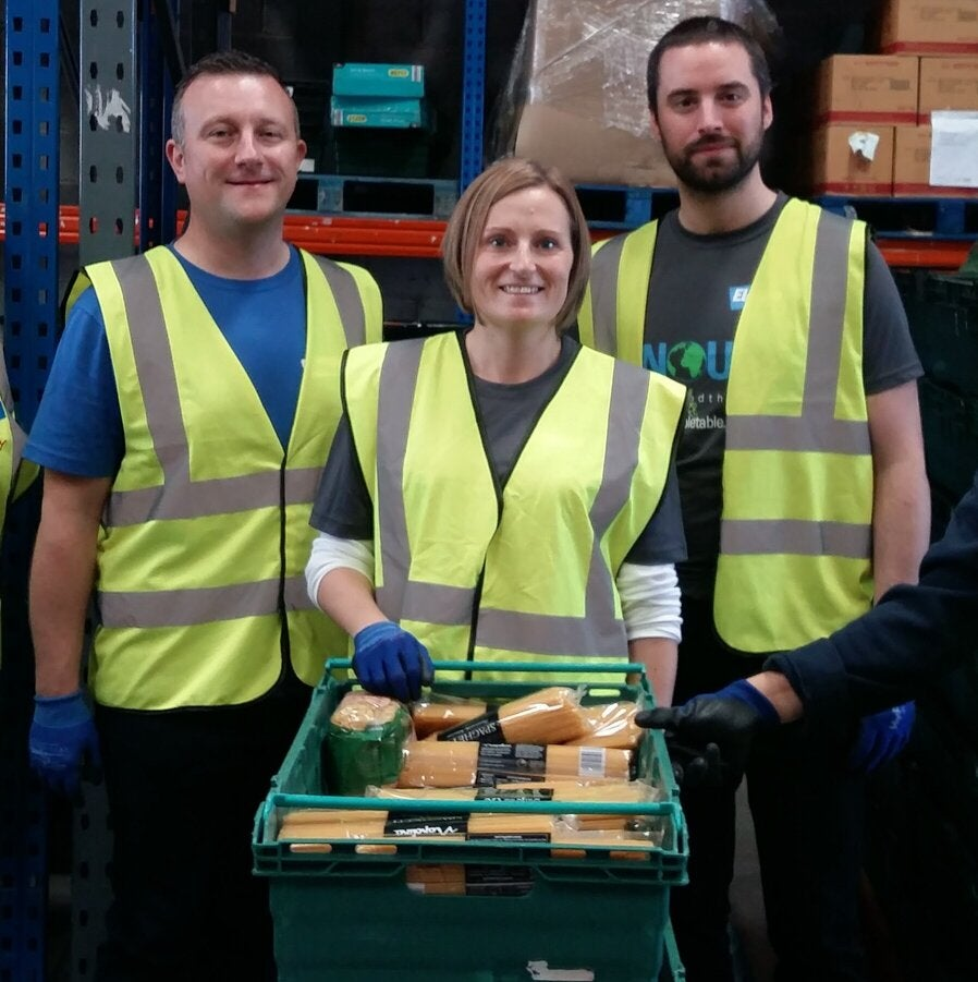 employees standing together while holding a basket of food