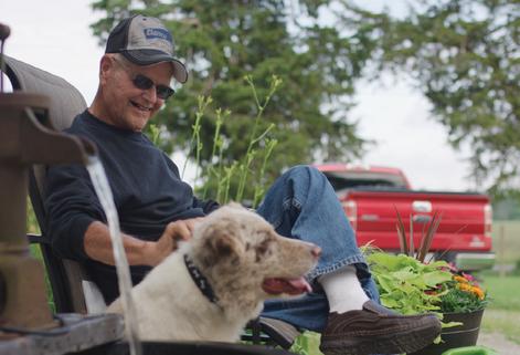man smiling while petting his dog