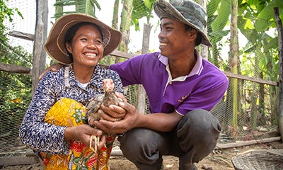 man and woman smiling and hugging knelt down whilst the woman is holding a chicken