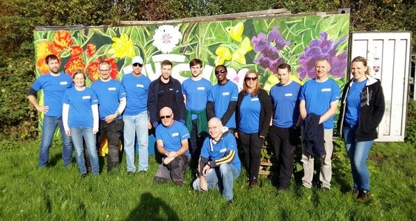 a group of employees standing together in front of a mural