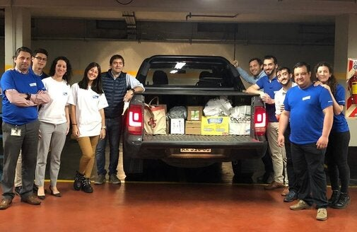 employees in front of a truck full of food and supplies