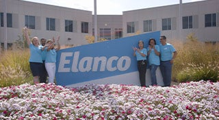 group of elanco employees by the elanco sign