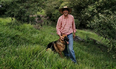 man walking through a field smiling at the camera whilst touching his dog