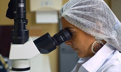 a woman in a lab with a hair net on looking into a microscope