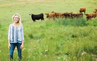 woman standing in a field of cattle