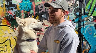young man looking at his dog and smiling infront of a graffiti wall