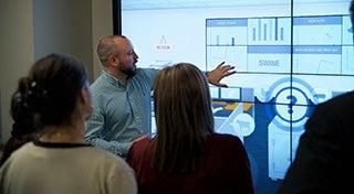 Ein Mann, der vor einer Gruppe von Menschen steht und auf ein interaktives Whiteboard zeigt