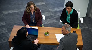 overhead view of three women and a man discussing at a table