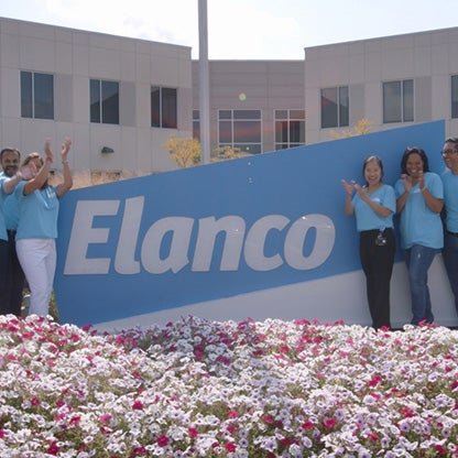 a group of five stood next to an Elanco animal health sign outside in front of flowers