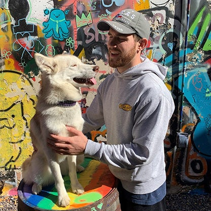 a young man looking and stroking his dog in front of a graffiti wall