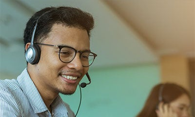 man smiling with a headset on in a office