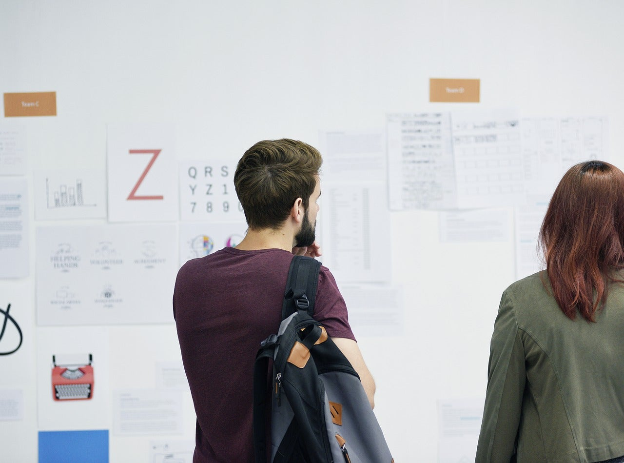 Two Product Managers Looking at plans on a white board.