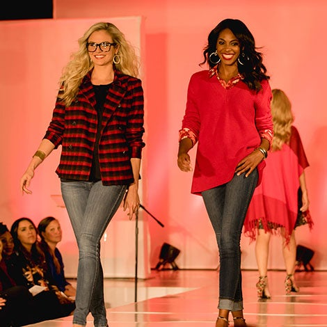 Two stylish women walking down runway