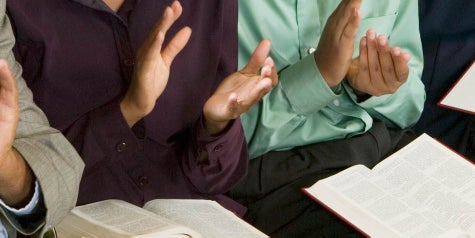 Church members sitting in a pew clapping hands to worship with Bibles in lap.