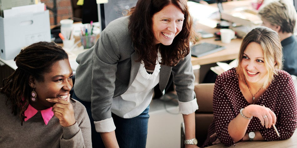 Three diverse women smiling and communicating in a work meeting.