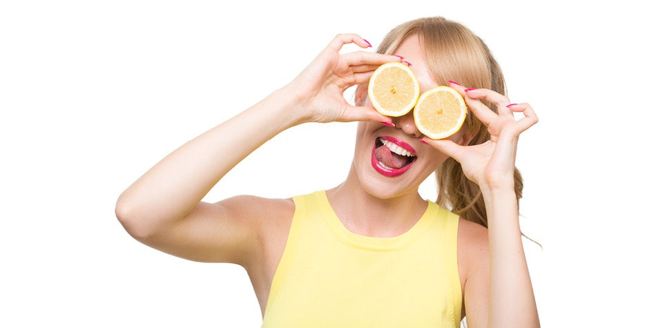 Young lady holding oranges cut in half in front of here eyes smiling.