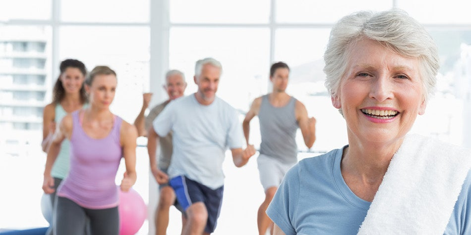 Fitness group class with elderly lady in front smiling.