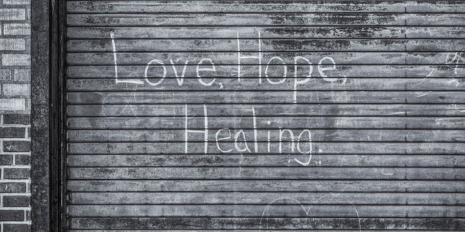 Words of love, hope and healing written on an outdoor garage door
