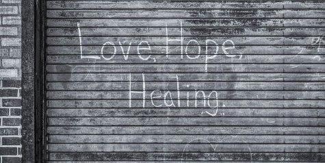 Words of love, hope and healing written on an outdoor garage door
