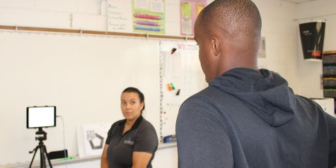 Athletic trainer giving a vision test to student athlete.