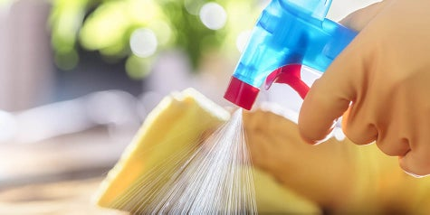 spray bottle and gloves cleaning and disinfecting